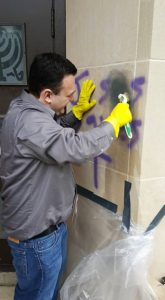 Cedar Valley Atheists member, Jacob Madden scrubs graffiti from the walls of Sons of Jacob Synagogue in Waterloo, Iowa